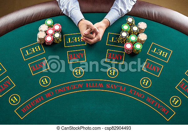 Closeup of poker player with chips at green casino table - csp82904493