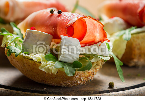 Closeup of sandwiches made of parma ham and brie cheese - csp16844728