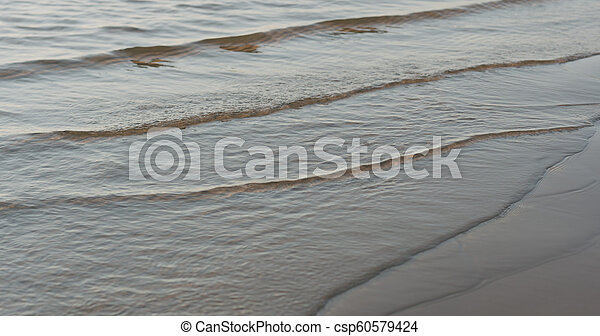 closeup of small waves on a beach at sunset - csp60579424