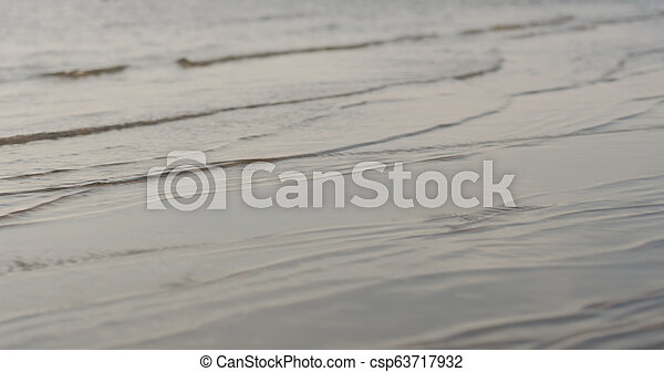 closeup of small waves on a beach at sunset - csp63717932