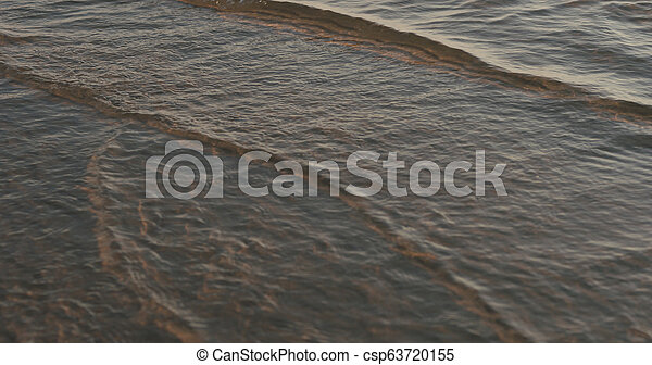 closeup of small waves with caustics on a beach at sunset - csp63720155