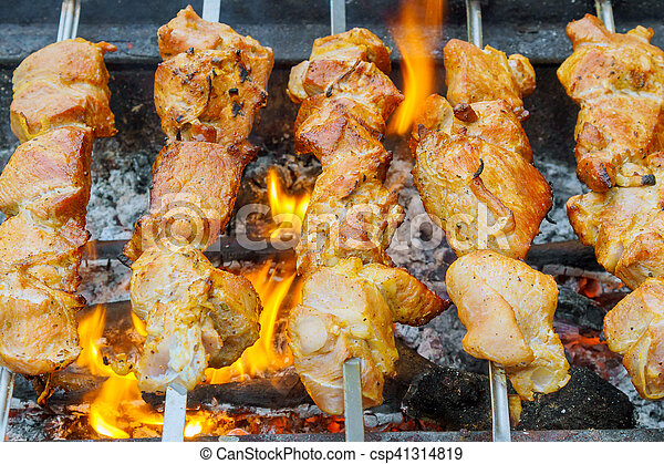 closeup of some meat skewers being grilled in a barbecue - csp41314819