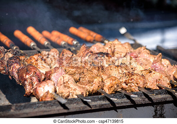 closeup of some meat skewers being grilled in a barbecue - csp47139815