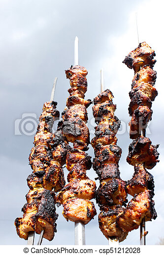 closeup of some meat skewers being grilled in a barbecue - csp51212028
