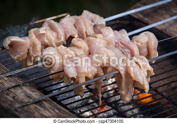 Closeup of some meat skewers being grilled in a barbecue - csp47304105
