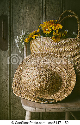 Closeup of sunflowers in straw purse on chair - csp61471150