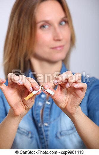 Closeup of woman breaking cigarette - csp9981413