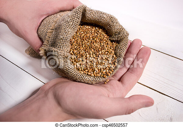 Closeup of young man's hands holding a sack with a buckwheat on white wooden table - csp46502557
