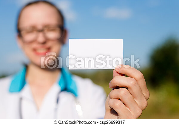 closeup on business card: female doctor holding and showing blank card happy smiling & looking at camera on blue sky copy space background outdoors - csp26699317