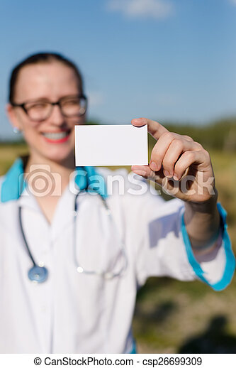 closeup on business card: female doctor holding and showing blank card happy smiling & looking at camera on blue sky copy space background outdoors - csp26699309