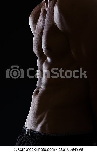 Closeup on muscular male torso with abdominal muscles on black - csp10594999