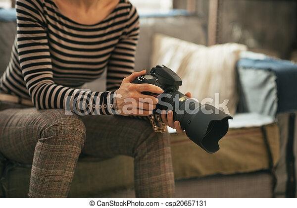 Closeup on young woman with modern dslr photo camera - csp20657131