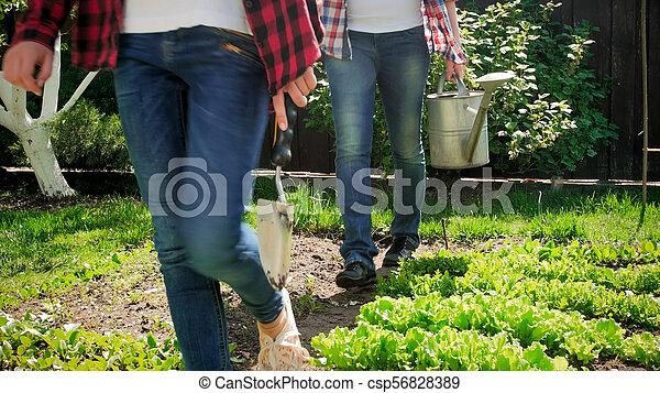 Closeup photo of family walking at backyard garden with gardening tools - csp56828389