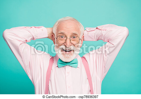 Closeup photo of funny grandpa positive cheerful facial expression good mood arms behind head wear specs stylish pink shirt suspenders bow tie isolated teal color background - csp78936397