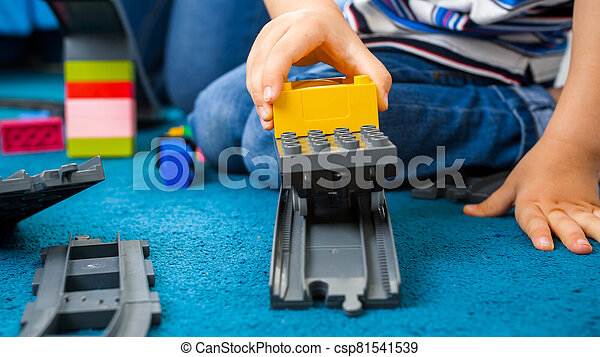 Closeup photo of little toddler boy playing woth toy train and railroad on carpet at playroom - csp81541539
