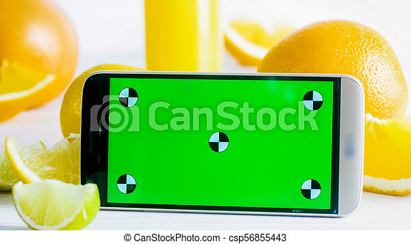 Closeup photo of mobile phone with green chromakey screen next to fresh fruits on white table. Perfect for inserting your own photo - csp56855443