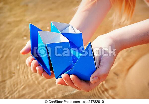 Closeup photo of paper ship in children hand - csp24782010
