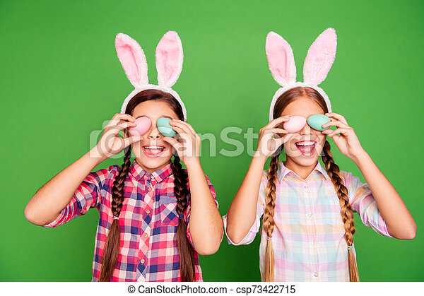 Closeup photo of two cute sweet lovely with open mouth long haired in checkered casual shirt outfit holding colorful eggs in hands isolated bright vibrant background - csp73422715