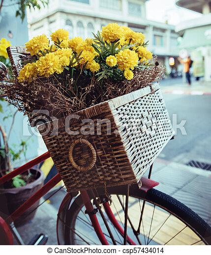 Closeup picture of a vintage bike with flowers in a basket - csp57434014