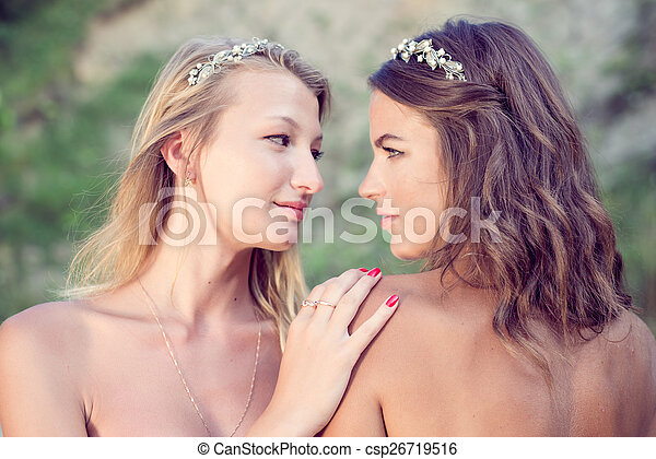 closeup portrait of 2 brunette and blonde young pretty women best friends with bare shoulders wearing silver diadems looking at each other on green summer outdoors background - csp26719516