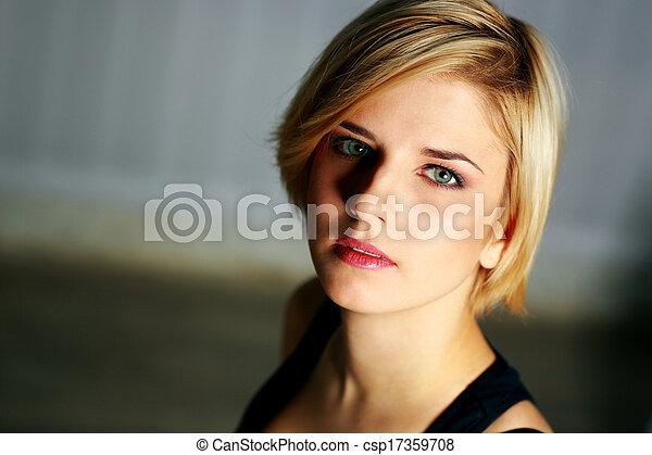 Closeup portrait of a young pensive woman looking at camera - csp17359708