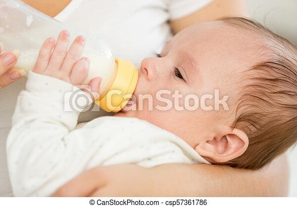 Closeup portrait of adorable baby boy sucking milk from bottle - csp57361786