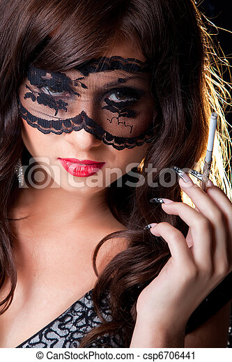 Closeup portrait of attractive young brunette girl with long dark ringlets and fine art manicure wearing lacy mask on her eyes holding graceful silver mouthpiece with thin ladies' cigaret on black ba - csp6706441