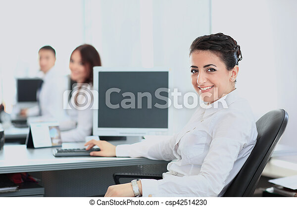 Closeup portrait of business woman giving you cute smile with colleagues in background - csp42514230