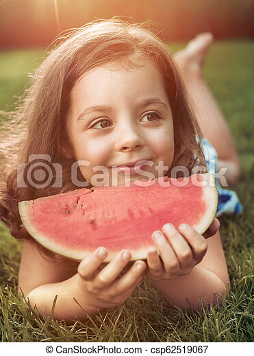 Closeup portrait of smiling girl holding watermelon slice in the garden - csp62519067