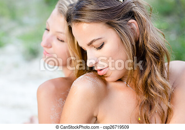 closeup portrait of two beautiful brunette and blonde young ladies best friends sitting back to back with bare shoulders on green summer outdoors background - csp26719509
