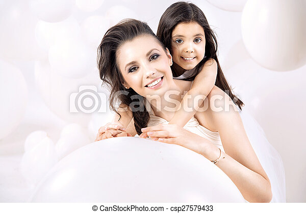 Closeup portrait of young mom with a cute daughter - csp27579433