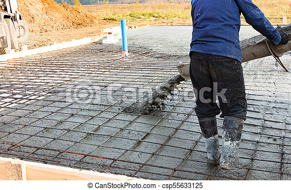 Closeup shot of concrete casting on reinforcing metal bars of floor in industrial construction site - csp55633125