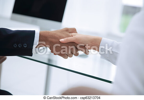 closeup .the financial partners shaking hands over a Desk . - csp63213704