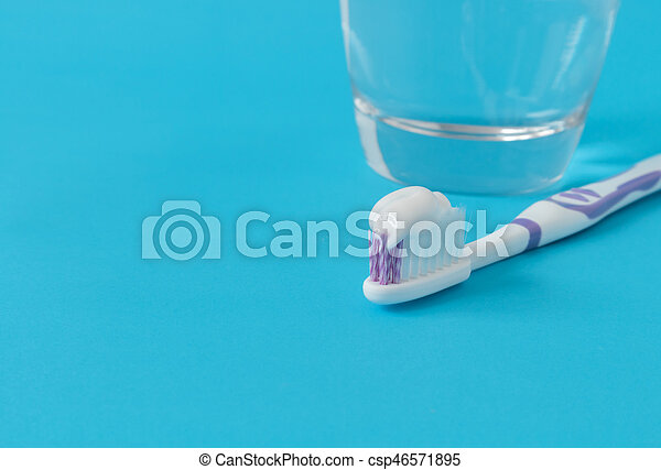 Closeup toothpaste on toothbrush with water glass on blue background - csp46571895