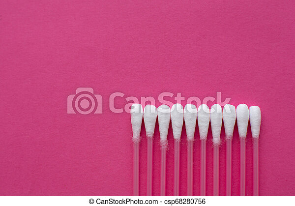 Closeup top view on cotton buds laid in a horizontal line on pink background - csp68280756