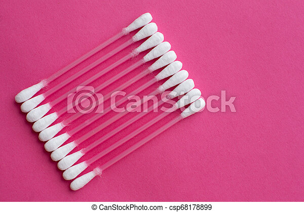 Closeup top view on cotton buds laid in a diagonal line on pink background - csp68178899