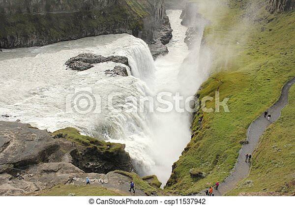 Closeup view from above on Iceland's Gulfoss waterfall with people watching the water falling into the canyon - csp11537942
