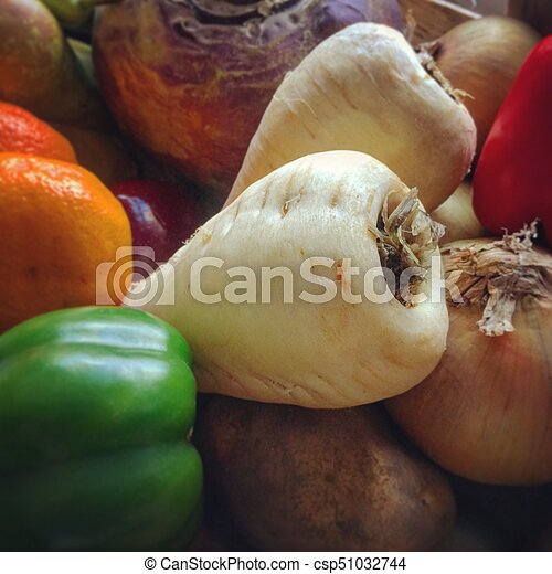 Closeup view on parsnips in a tray of seasonal fruit and vegetables - csp51032744