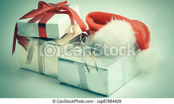 closeup.boxes with gifts and a Santa Claus hat. - csp87884429