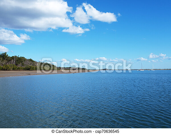 Cloud over land and water with blue sky. - csp70636545