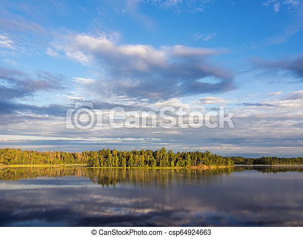 clouds over a forest lake - csp64924663