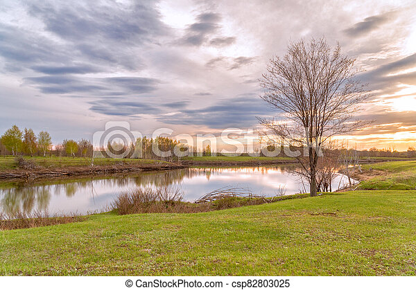 Clouds over the autumn lake in evening - csp82803025