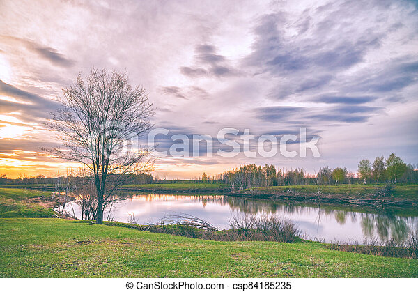 Clouds over the autumn lake in evening - csp84185235