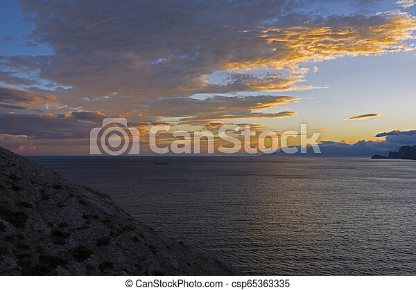 Clouds over the sea illuminated by the setting sun. - csp65363335
