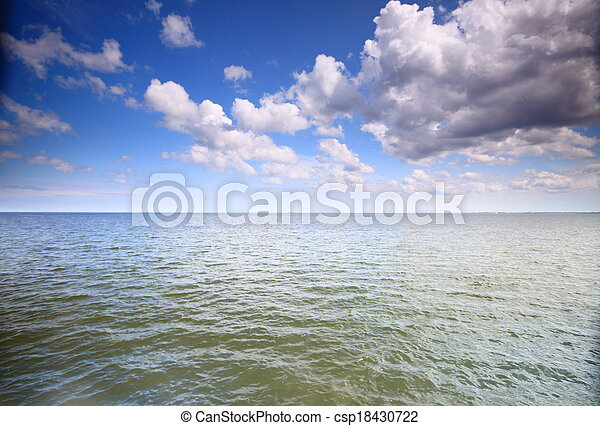 Cloudy blue sky above a surface of the sea - csp18430722