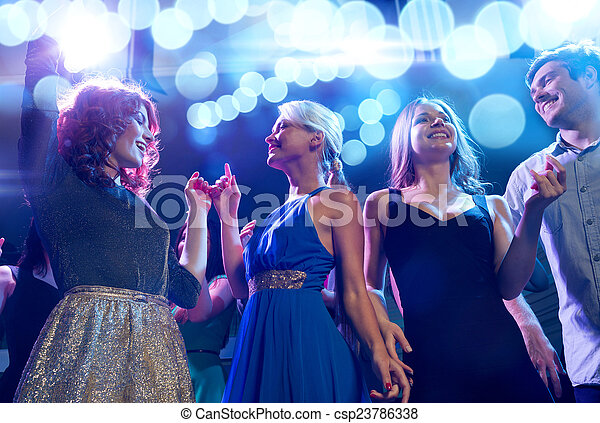 Amigos sonrientes bailando en el club - csp23786338