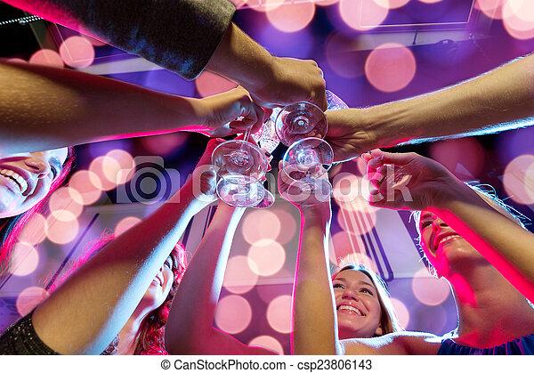 Amigos sonrientes con copas de champán en el club - csp23806143