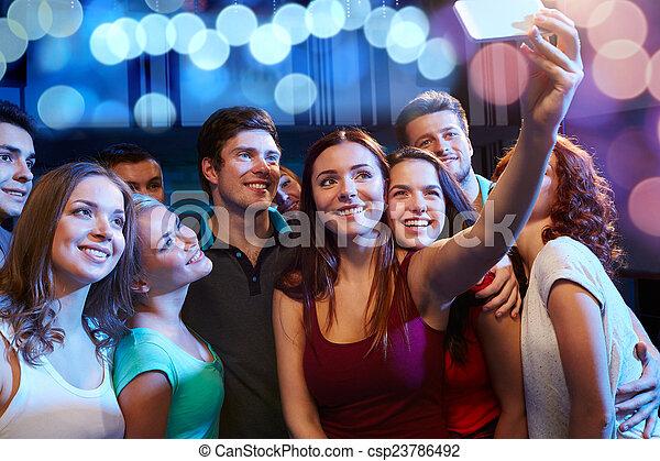 Amigos con smartphone tomando selfie en el club - csp23786492