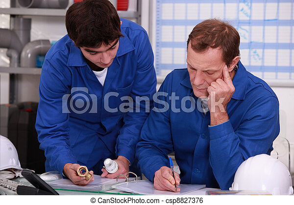 Co-workers checking reference of a piece - csp8827376