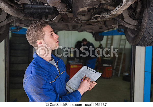 Mecánico bajo el auto preparando la lista - csp11961187